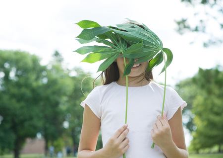 Girl standing holding cassava leaves in front of face
