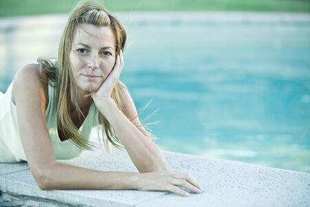 Woman lying by edge of pool