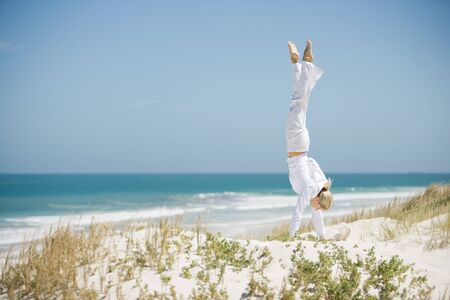 Young woman doing handstand in dunes, ocean in background LANG_EVOIMAGES