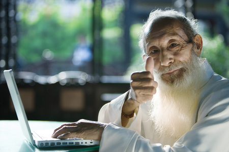 Elderly man wearing traditional Chinese clothing, using laptop, giving thumbs up to camera