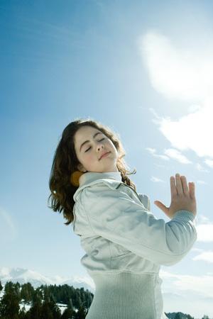 Das jugendlich Mädchen, das in der schneebedeckten Landschaft mit Augen steht, schloss und Hände umklammert