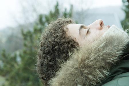 Teen boy wearing parka, head back and eyes closed
