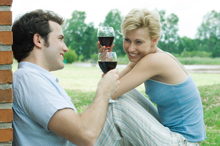 Couple sitting outdoors, toasting with glasses of red wine