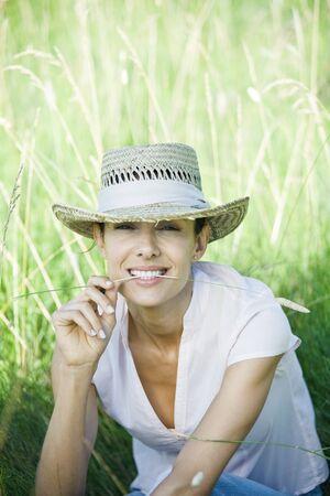percepción: Woman in field, blade of grass between lips, looking at camera