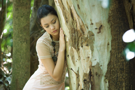 beauties: Young woman leaning head against tree trunk, eyes closed LANG_EVOIMAGES