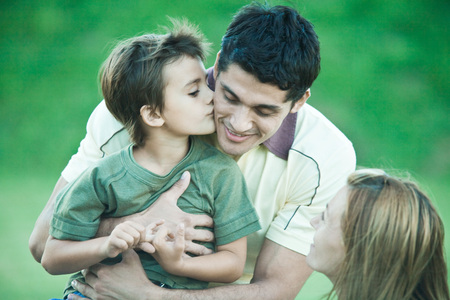 smooching: Boy with parents, kissing father on cheek LANG_EVOIMAGES