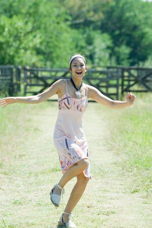 Young woman running along rural path, smiling at camera