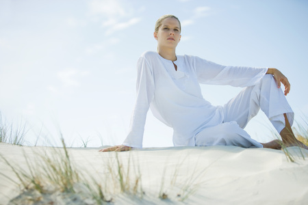 Young woman sitting on dune, low angle view LANG_EVOIMAGES