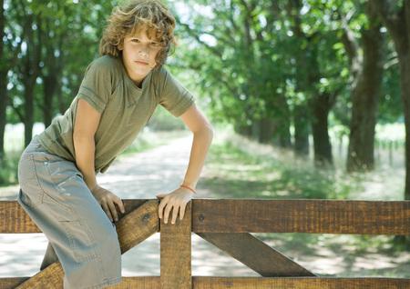 Boy climbing fence, looking at camera