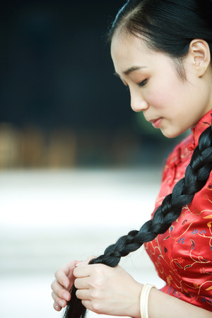 Young woman wearing traditional Chinese clothing, holding long braid LANG_EVOIMAGES
