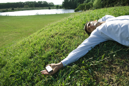 Businessman lying on grass, holding cell phone