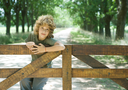 Boy hanging on fence