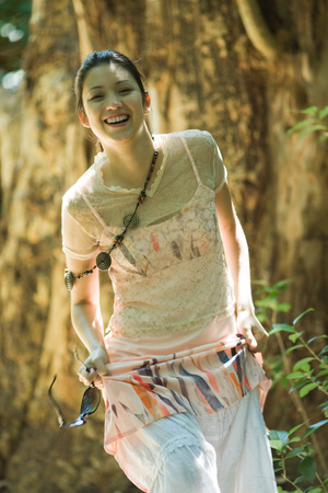 Young woman walking in woods, holding up skirt, smiling at camera LANG_EVOIMAGES