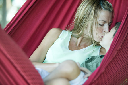 smooching: Boy and mother in hammock, kissing LANG_EVOIMAGES