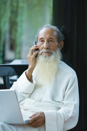 Elderly man wearing traditional Chinese clothing, using laptop and cell phone
