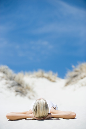 Young woman lying on beach, hands behind head LANG_EVOIMAGES