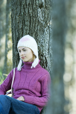 Young woman sitting on ground, leaning against tree, wearing knit hat and sweater