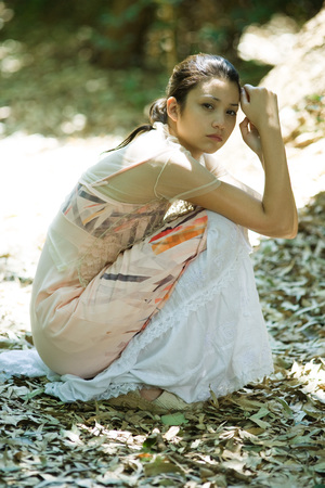 Young woman crouching in leaves, looking at camera LANG_EVOIMAGES