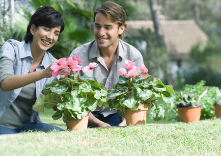 Couple tending potted plants LANG_EVOIMAGES