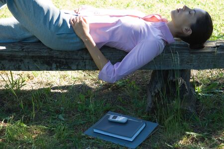Businesswoman lying on bench, outdoors LANG_EVOIMAGES
