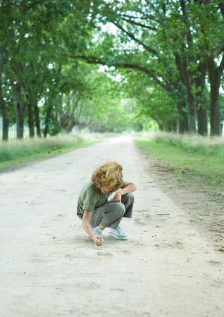 Boy crouching in middle of dirt road