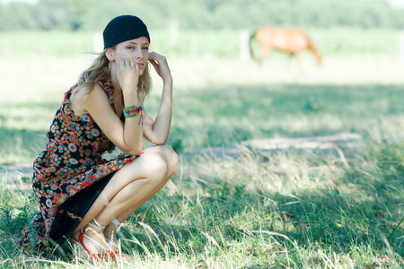 beauties: Young woman crouching in field, looking at camera