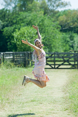 salto de valla: Young woman jumping with arms raised in rural setting, smiling at camera LANG_EVOIMAGES