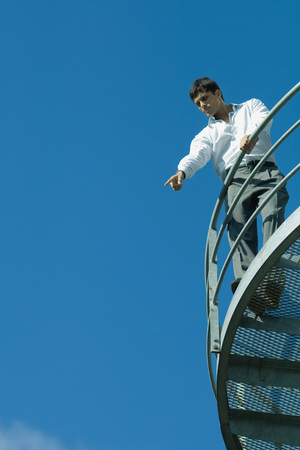 accusations: Businessman standing on metal balcony, pointing down, low angle view, blue sky in background