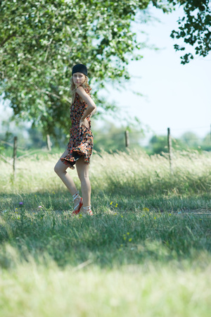 Young woman walking along rural path, looking over shoulder LANG_EVOIMAGES