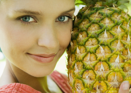 beauties: Woman holding up pineapple to face