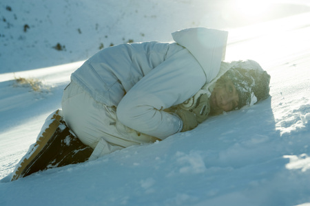 Teen girl curled up on snow, smiling at camera