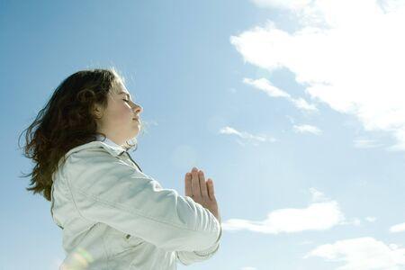 Das jugendlich Mädchen, das mit den Händen in der Gebetsposition und in Augen steht, schloss, niedrige Winkelsicht LANG_EVOIMAGES