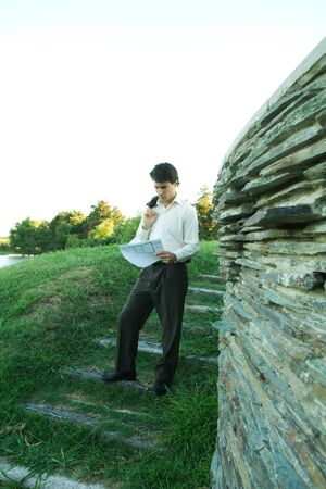 Man standing near stone wall, holding blueprints