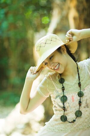 beauties: Young woman standing outdoors, putting on sunhat, smiling