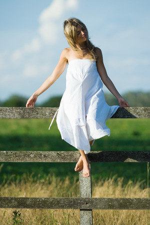 Young woman in dress sitting on rural fence with arms out, eyes closed