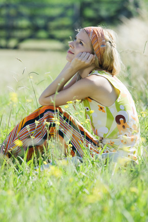Young woman sitting in tall grass with knees up, holding head and looking up