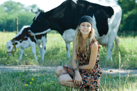 vestidos de epoca: Young woman crouching in front of cows, smiling at camera LANG_EVOIMAGES