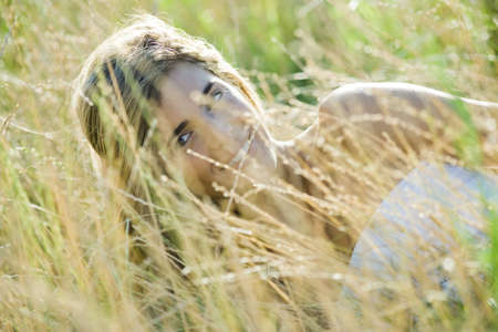 Young woman reclining in tall grass, smiling