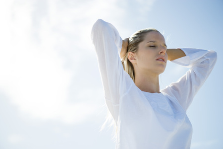 Young woman standing with sky in background, pushing hair back, eyes closed, low angle view