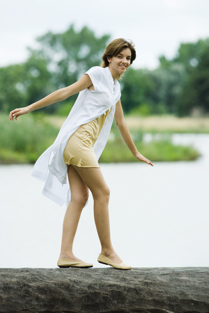 Young woman walking across log with arms out, smiling at camera LANG_EVOIMAGES