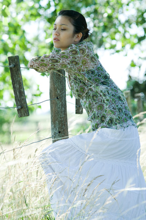chainlink fence: Young woman leaning against rural fence, looking away