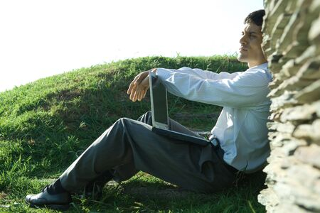 distractions: Businessman sitting on ground, holding laptop, looking away LANG_EVOIMAGES