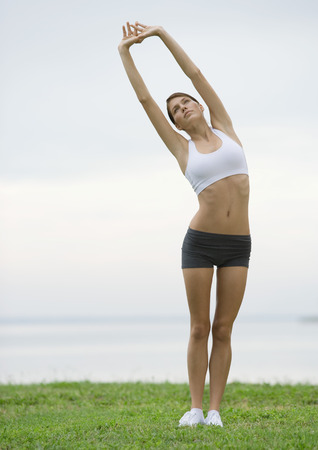 Young woman doing stretching exercises by lakeside LANG_EVOIMAGES