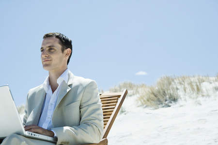 Businessman sitting in deck chair at beach, using laptop LANG_EVOIMAGES