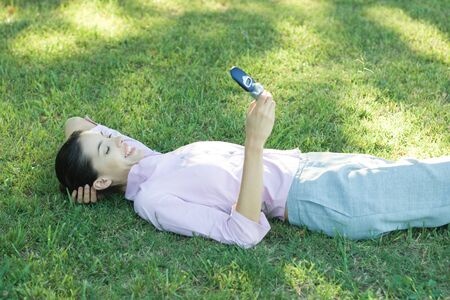 Businesswoman lying in grass, looking at cell phone, smiling