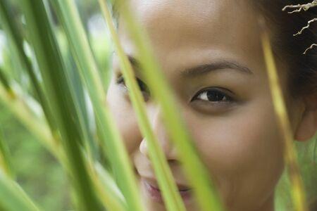 Mujer detrás de las hojas, recortada LANG_EVOIMAGES