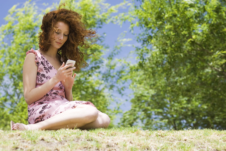 Young woman sitting outdoors, text messaging