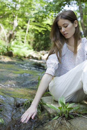 Young woman touching stream water