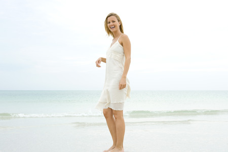 Young woman standing on beach in sundress, laughing