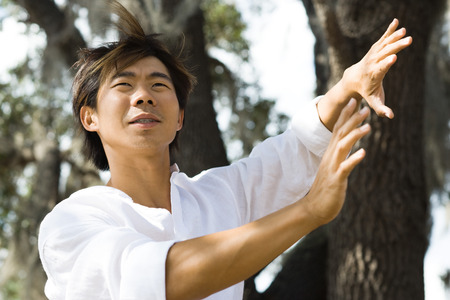Man standing outdoors with hands raised, hair tousled by breeze, low angle view